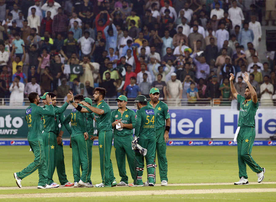 Pakistan's players celebrate taking a wicket during the first T20I match between Pakistan and West Indies at the Dubai International Cricket Stadium on September 23, 2016. / AFP / KARIM SAHIB        (Photo credit should read KARIM SAHIB/AFP/Getty Images)